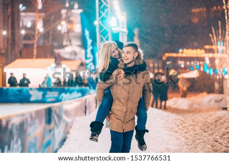 Cheerful and playful couple in warm winter outfits are fooling around #1537766531