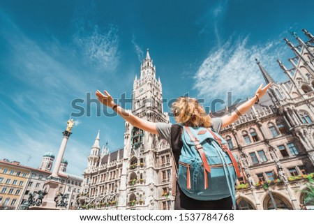 A girl tourist traveler enjoys a Grand view of the Gothic building of the Old town Hall in Munich. Sightseeing and exploration of Germany concept Royalty-Free Stock Photo #1537784768