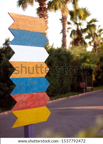 Colorful pointers on the background of the park. Signpost directional arrows. Direction sign, empty frame for designers #1537792472