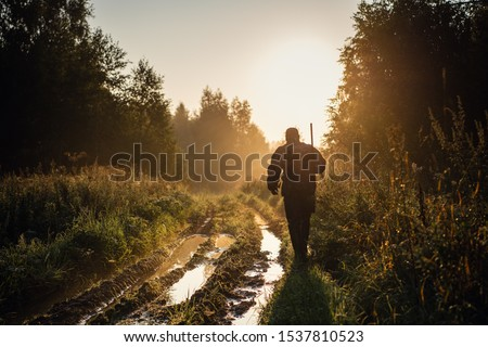 Vintage hunter walks the forest road. Rifle Hunter Silhouetted in Beautiful Sunset or Sunrise. Hunter aiming rifle in forest #1537810523