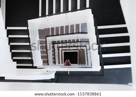 A high angle shot of spiral staircases and a female taking a picture during daytime