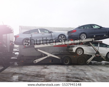 Loading new cars from automobile plant on the truck for delivery to customers. Winter sunnyday is wet snow. The trailer transports cars on highway. Logistics company carrier delivers to the customer. #1537945148