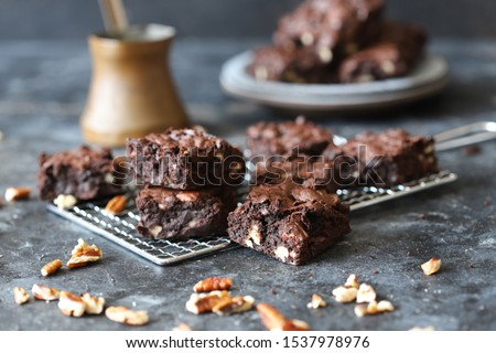 Homemade fudgy chocolate brownies on grey background. chocolate walnut brownie cake still life #1537978976