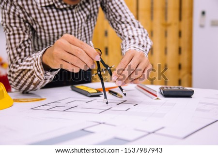 Engineer man and Architect drawings blueprint at Construction Site.Home Project to Offer Management #1537987943