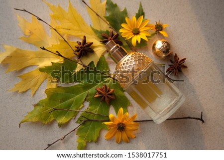 glass perfume bottle with a gold insert with autumn leaves. twigs, yellow flowers and anise stars #1538017751