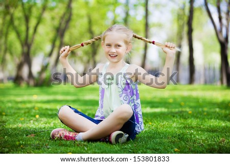 Image of little cute girl sitting on grass in park #153801833