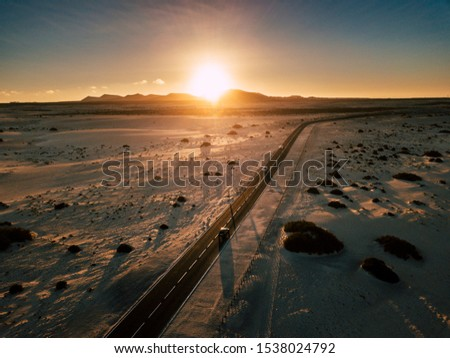 Travel concept with long black asphalt road crossing the landmark and desert with sunlight sunset in backgorund -drive and move with vehicles on scenic road #1538024792