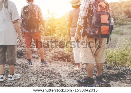 Group of four retired senior friends walk together as a team, travel adventures, carry a backpack behind, study nature and mountains with physical, healthy bodies, watch the sunset.  #1538042015