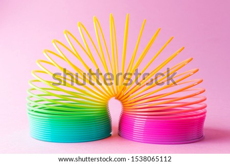 Toy plastic rainbow on a pastel pink background. A colored spiral for play and stunts, popular in the 90s.  Minimalism. The concept of toys, childhood. brightness. #1538065112