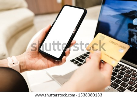 Close up of man using blank cell phone,laptop and credit card sending massages shopping online or reporting lost card, fraudulent transaction within the coffee shop