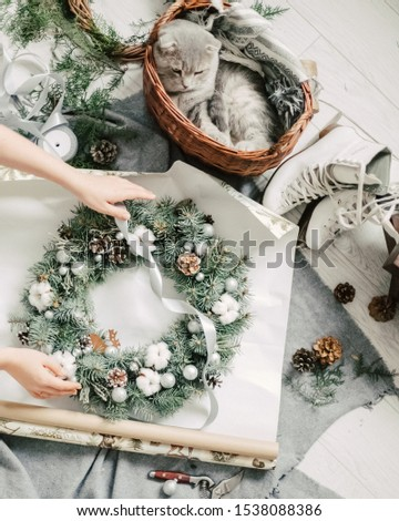 Overhead view of Christmas wreaths being made. Christmas wreath weaving workshop. Woman hands decorating holiday wreath made of spruce branches, cones and various organic decorations on the table #1538088386