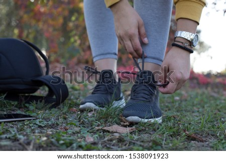 Beautiful young Hispanic woman tying her shoes #1538091923