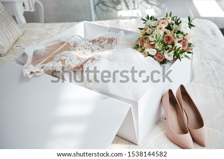 Luxury wedding dress in white box, beige women's shoes and bridal bouquet on bed, copy space. Bridal morning preparations. Wedding concept #1538144582