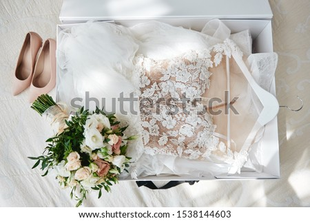 Luxury wedding dress in white box, beige women's shoes and bridal bouquet on bed, copy space. Bridal morning preparations. Wedding concept Royalty-Free Stock Photo #1538144603