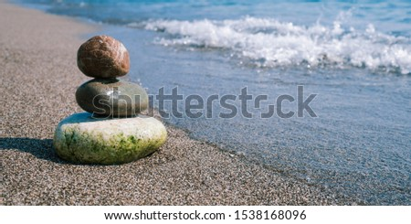Stack of zen stones on beach near sea. Tower of spa rocks on sand at ocean. Balanced pebbles outdoors on sunny summer day. Oriental calm and harmony symbol. Wellness and tranquility concept #1538168096