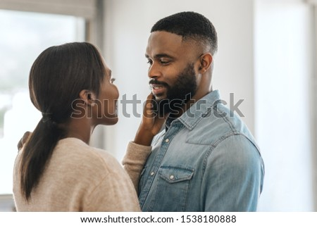Young African American man smiling and looking at his wife while standing arm in arm together in their modern apartment #1538180888