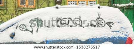 Dirty car in the snow on a village street, funny pictures in the snow by car
