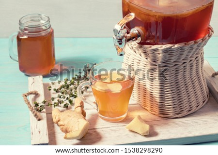 Fresh homemade kombucha fermented tea drink in a jar with faucet and in a cup and in mug on a white tray on a wooden background