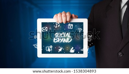 Young business person working on tablet and shows the inscription: SOCIAL BRAND #1538304893