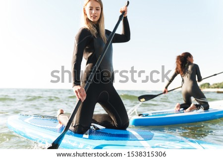 Picture of a young pretty two women on a kayaks outdoors at the beach.