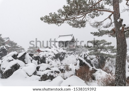 Onioshidashi Park under heavy snow - snow covered volcanic rocks with a tree and bell in the back #1538319392