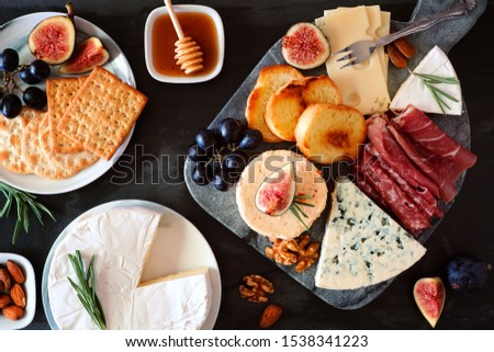 Platter of assorted cheeses and cold cut meats. Top view table scene on a dark background. #1538341223