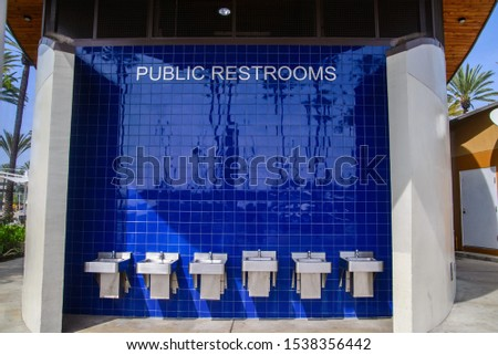 simple design of a public restrooms. washroom on open air by the restroom. blue tiles wall #1538356442