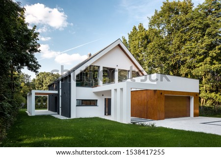 Exterior view of modern, white house with garage decorated with wood Royalty-Free Stock Photo #1538417255