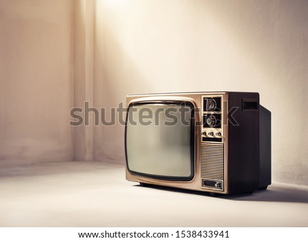 Old retro TV in an empty white room. Vintage filter effect #1538433941