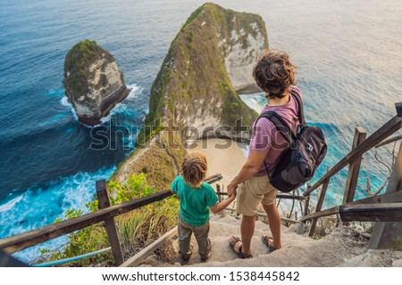 Family vacation lifestyle. Happy father and son stand at viewpoint. Look at beautiful beach under high cliff. Travel destination in Bali. Popular place to visit on Nusa Penida island