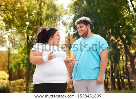 Overweight couple in sportswear together in park #1538451809