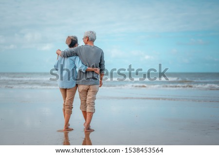 Senior couples walking on the beach at sunny day, plan life insurance with the concept of happy retirement. Royalty-Free Stock Photo #1538453564