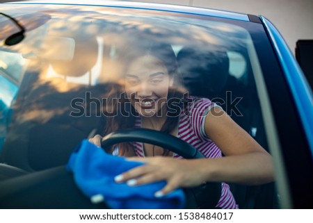 Young woman cleaning her car indoors.Transportation self service, care concept. Cleaning car interior. Woman with microfiber cloth cleaning car. Young woman cleaning auto. #1538484017