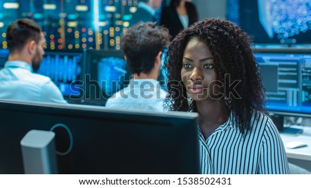 Female Computer Engineer Works on a Neural Network/ Artificial Intelligence Project with Her Multi-Ethnic Team of Specialist. Office Has Multiple Screens Showing 3D Visualization. #1538502431