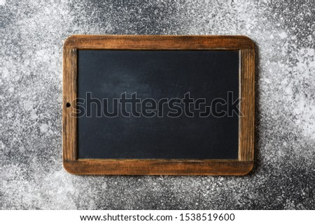 Small empty chalkboard on a grey textured background. Blank. Blackboard Background. Blackboard texture #1538519600