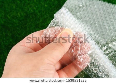 The hand touches the bubble wrap. The concept of touch, tactility, feelings. #1538531525