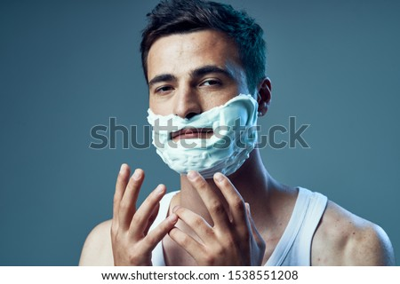 Handsome man with shaving foam on his face gesticulating with his hands #1538551208