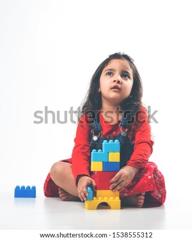 Cute Little Indian / Asian girl playing with colourful block toys over white background #1538555312