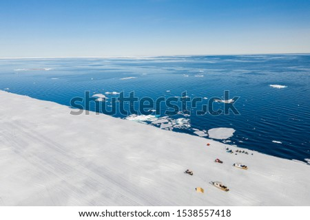 Aerial drone photo of tourists visit the floe edge near Sirmilik National Park in Nunavut, Canada #1538557418