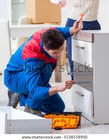 Contractor repairman assembling furniture under woman supervisio #1538558900