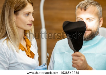 Man looking on the dental mirror, satisfied with his teeth, during a medical consultation with female dentist at the dental office #1538562266