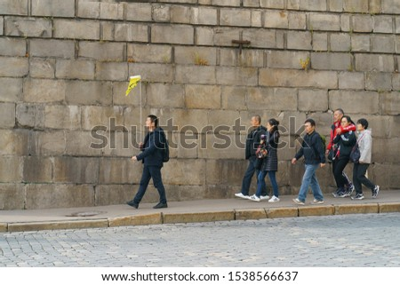 Moscow, Russia - October 18, 2019: Photography of a group of Chinese tourists, leds by a guide with yellow flag, head for a tour of Red Square in autumn day. Touristic concepts. #1538566637