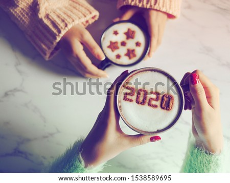 Coffee cup with the number 2020 on frothy surface in female hands holding over blurred marble table background and another one with star symbols on frothy surface. Happy new year 2020 food art theme. #1538589695