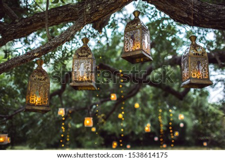 Evening wedding ceremony with a lot of vintage lanterns, lamps, candles. Unusual outdoor ceremony decoration. Beautiful garden party concept. #1538614175