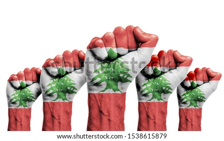 A raised fist of a protesters painted with the Lebanon flag Royalty-Free Stock Photo #1538615879