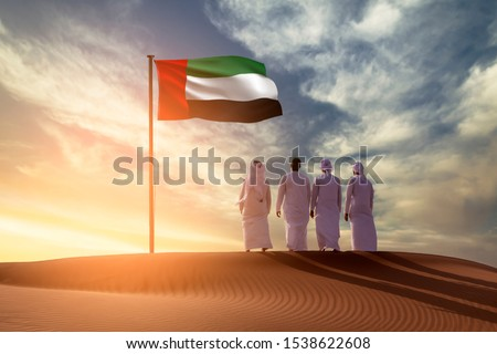Emirati Young men standing on sand dune on the desert looking in  UAE flag celebrating national day and Uae flag day #1538622608
