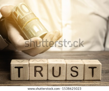 Wooden blocks with the word Trust and money in the hands of a businessman. Trust relationships between business partners, friends, relatives. Respect and authority. Confidence in a person. #1538625023