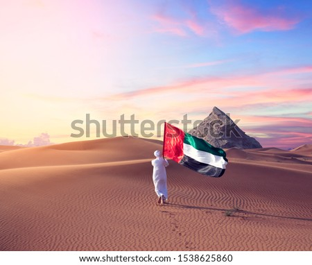 Emirati man holding UAE flag walking in the desert celebrate the national day - spirit of the union