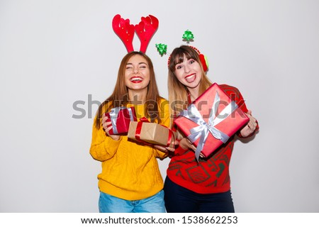 Image of surprised young women friends wearing christmas deer costumes standing isolated over white background wall. Looking at camera.
