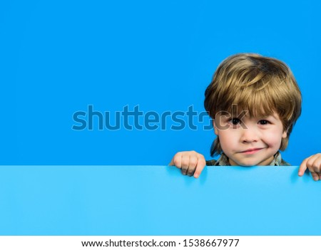 Boy holds blank sign. Child boy holds empty billboard. Little boy holds blank advertising banner. Funny little boy with empty board for your text. Blank sign for text. Advertising of children's goods.